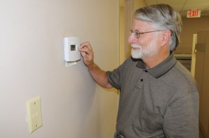 Man adjusts residential thermostat to save energy