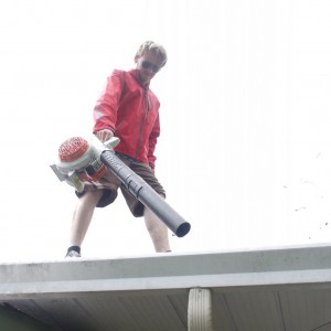 Cleaning gutter using blower.