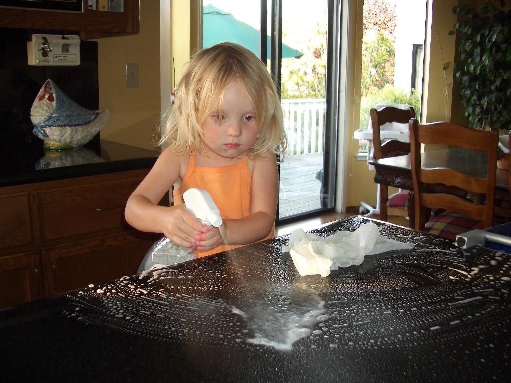 Baby girl cleaning kitchen countertop.