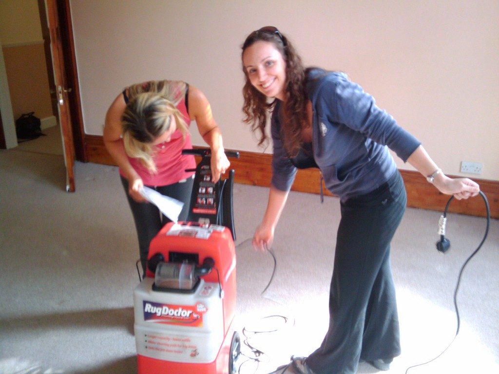 Sarah and Christina operating a brand new vacuum cleaner.