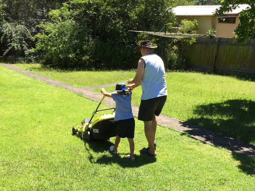Father and son does lawn mowing.